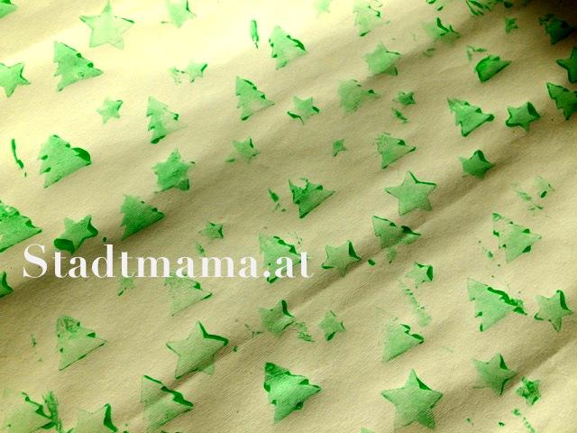 Bedrucktes Papier mit Tannenbäumen. Bastelanleitung Geschenkspapier bedrucken am 8. Dezember im Adventkalender von Babyspeck & Brokkoli. Gastbeitrag von Stadtmama.at,